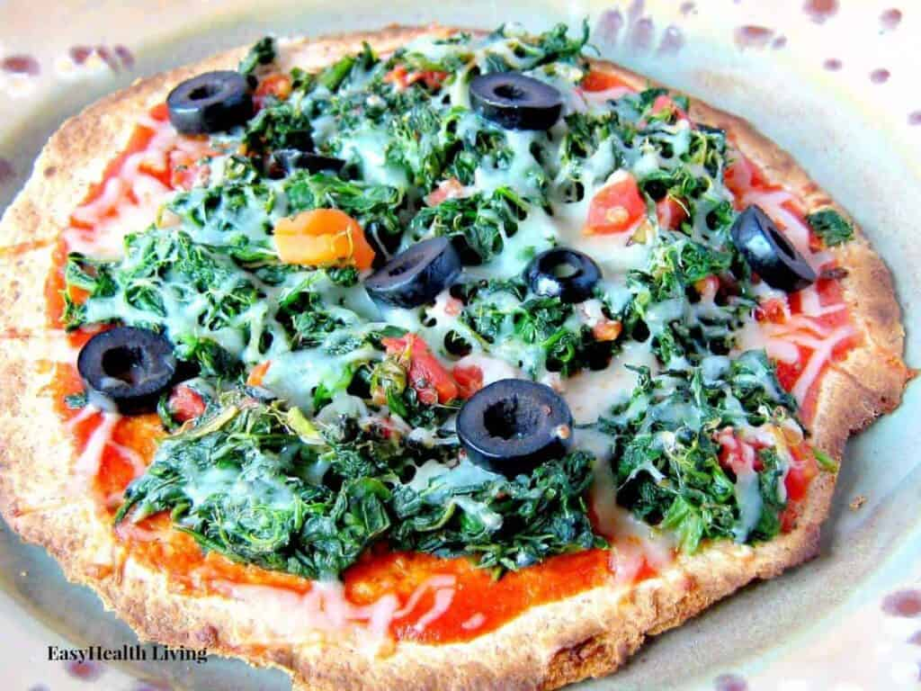 A multigrain tortilla topped with spinach, olives and roasted cherry tomatoes
