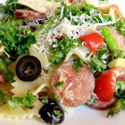 A plate of pasta salad with olives, kale and sausage