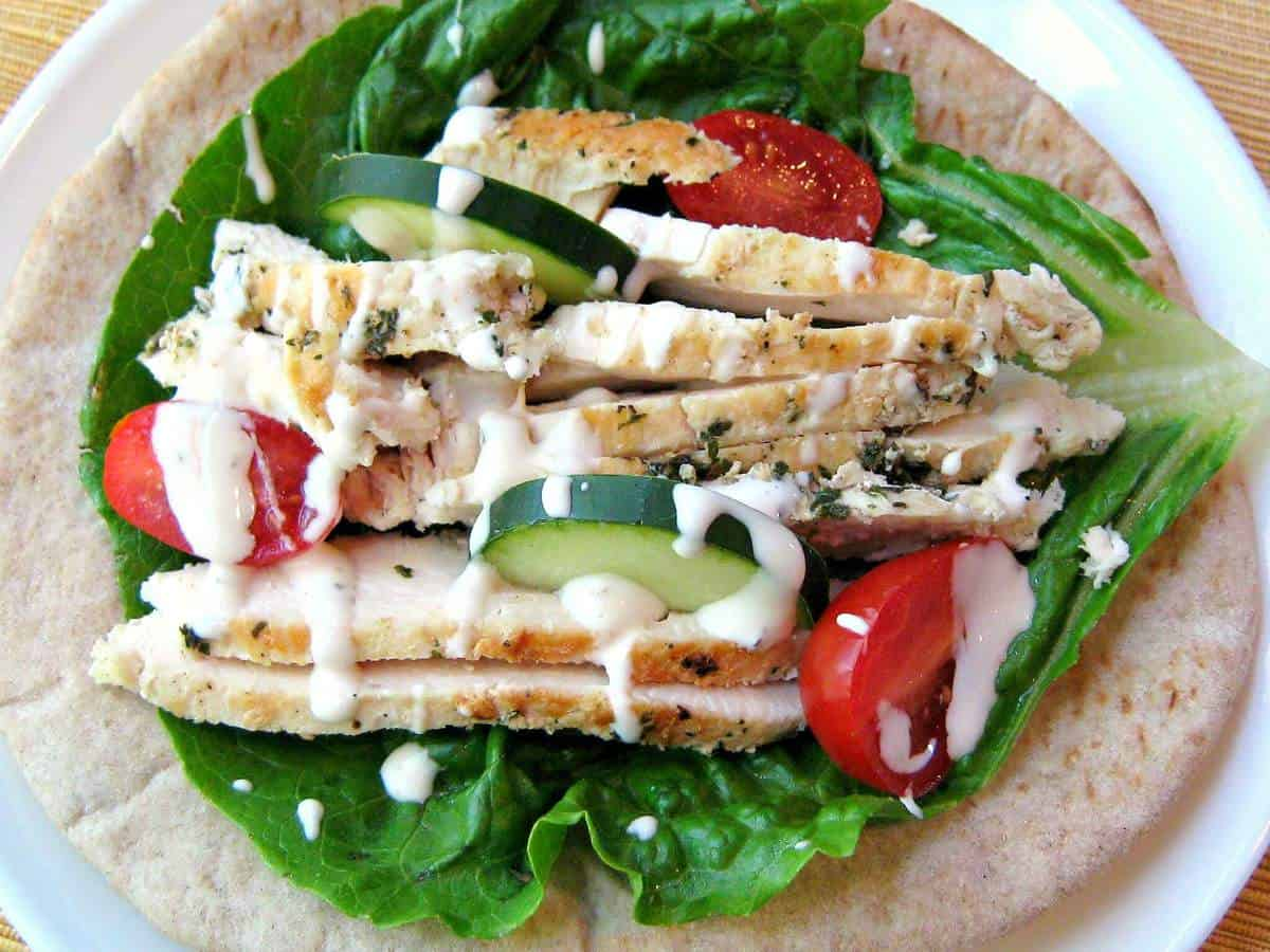 Greek chicken pita wrap uses delicious marinated Greek chicken recipe to create the perfect Mediterranean wrap!  Cook up a batch of chicken for a quick easy meal anytime. #greekchicken