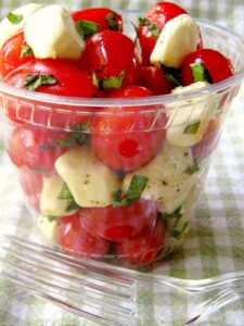 Picnic Tomato Caprese salad in clear cup with fork