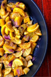 chopped yellow squash and onions in skillet