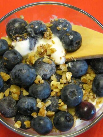 Blueberries and granola in cup with wooden spoon