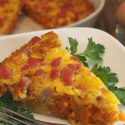 sweet potato tot and ham casserole wedge on white plate with parsley garnish