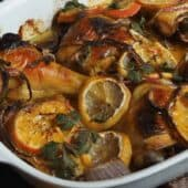 honey roasted chicken in pan with sliced oranges
