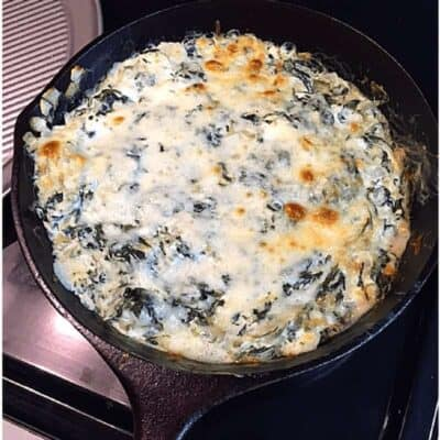 brown melted cheese on creamy spinach dip in black skillet