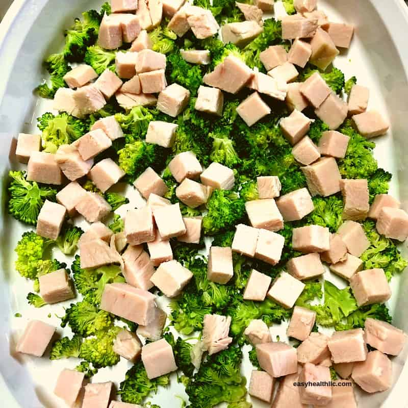 cooked chopped broccoli with turkey cubes in white casserole