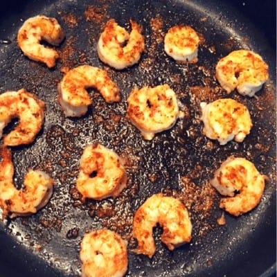 cajun seasoned shrimp cooking in skillet