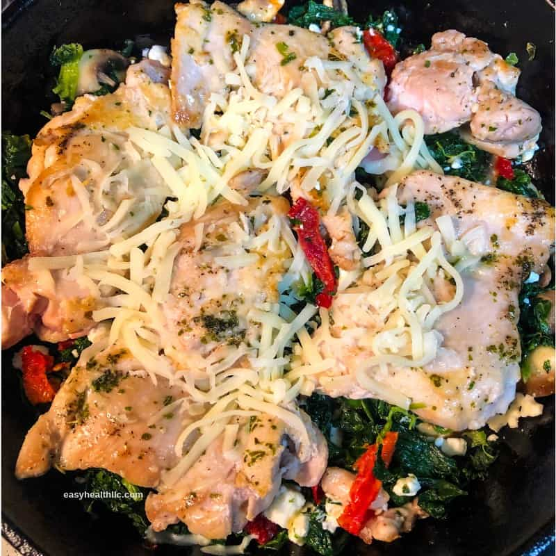 Mediterranean chicken on bed of spinach with cheese sprinkled on top