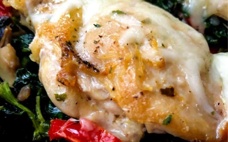 Greek chicken thigh with melted cheese on bed of spinach