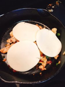 Provolone cheese slices melting over chicken and peppers