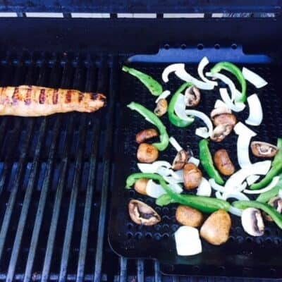 pork tenderloin on grill and grill rack with peppers, onions and mushrooms