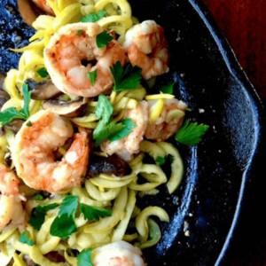 sautéed shrimp over squash noodles in skillet