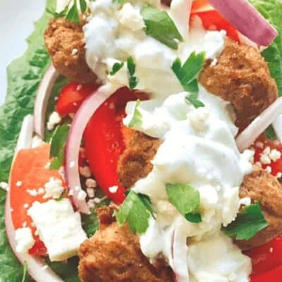 gyro meatballs on lettuce leaf with red onion and tzatziki sauce