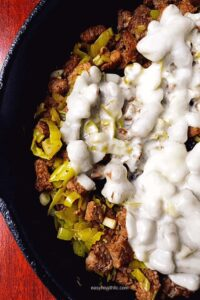 steak and pepperoncini and melted white cheese in skillet
