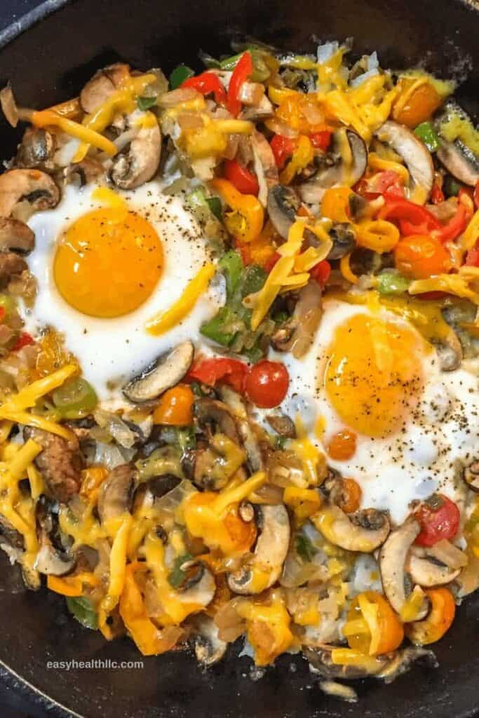 breakfast hash with 2 eggs in iron skillet