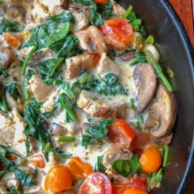chicken alfredo in iron skillet on wooden table