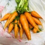 bunch of baby carrots with green tops