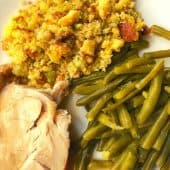 white plate with green beans, stuffing and turkey slice