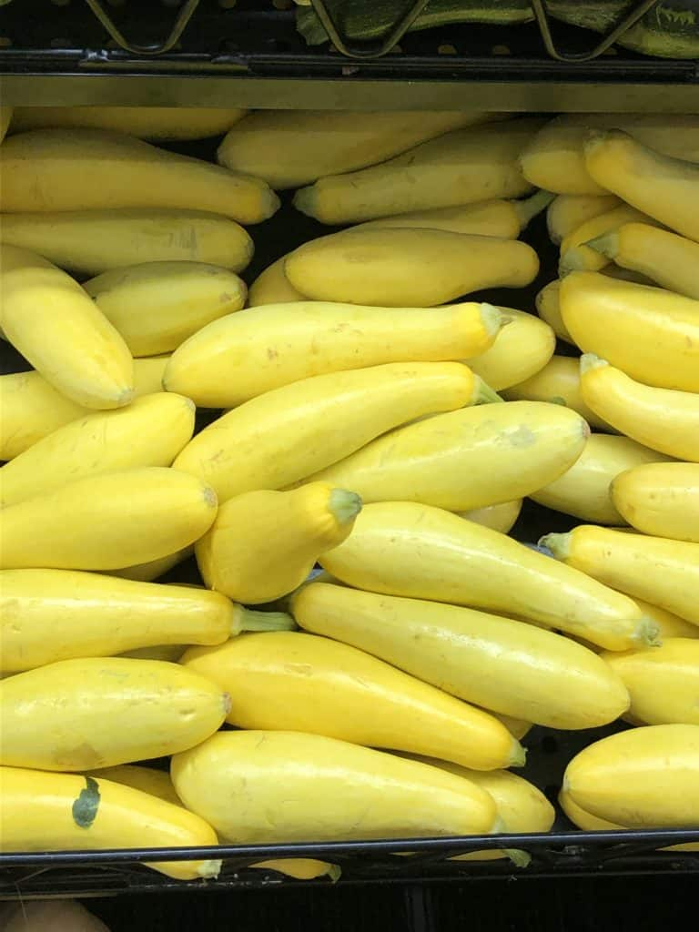 Yellow squash stacked in a bin in grocery.