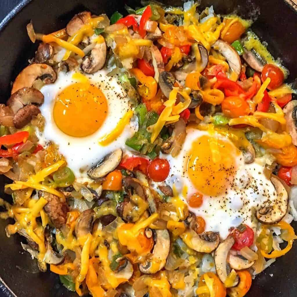 A black skillet filled with meat and vegetables, with Egg and Potato