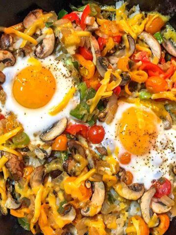 potatoes, veggies and eggs in black skillet