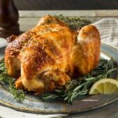 rotisserie chicken on a platter with lemon and herbs