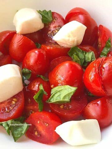 tomatoes, mozzarella salad in white bowl
