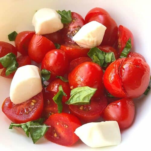 tomatoes, mozzarella salad in white bowl