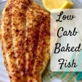 baked fish on plate with lemon wedge