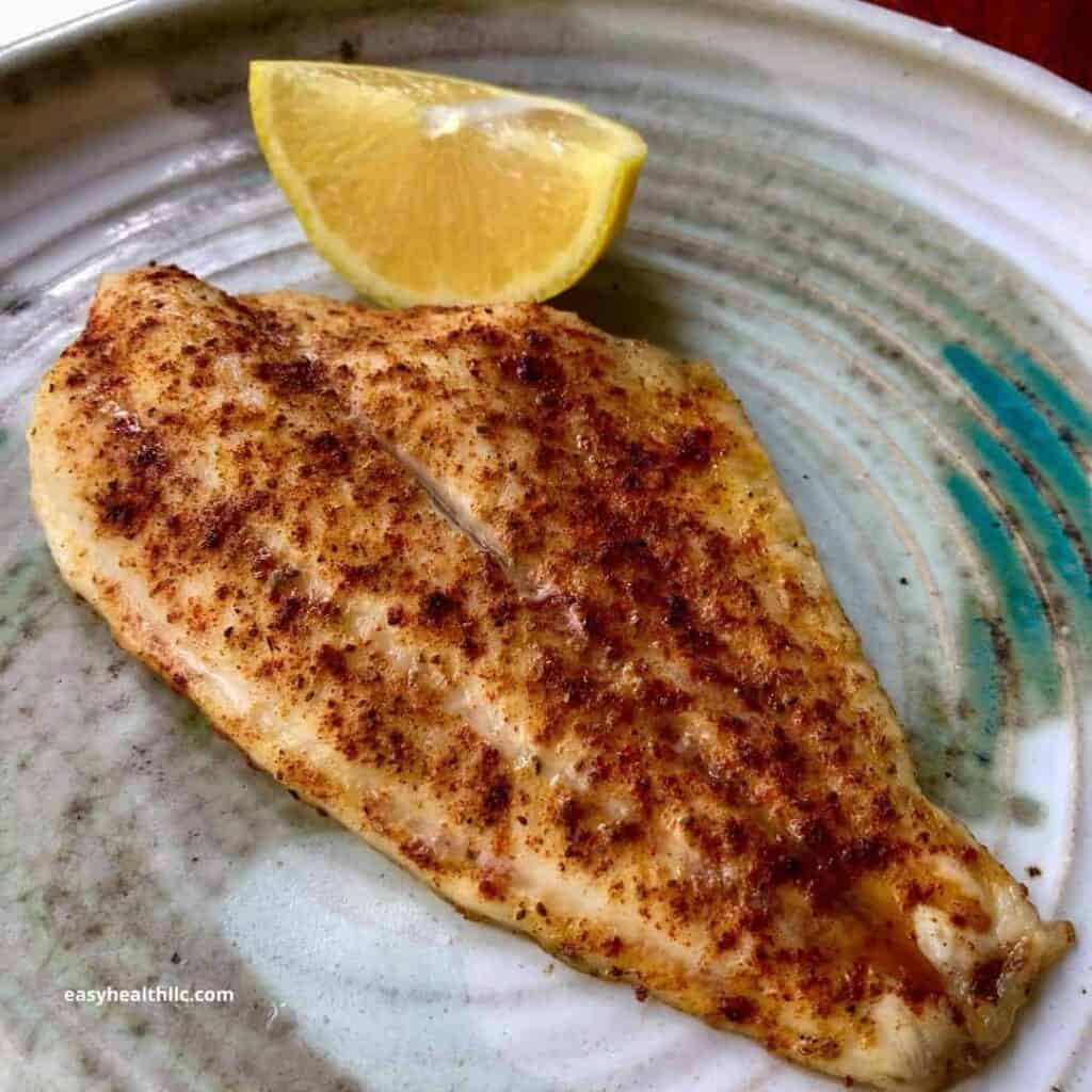 baked fish on plate with lemon