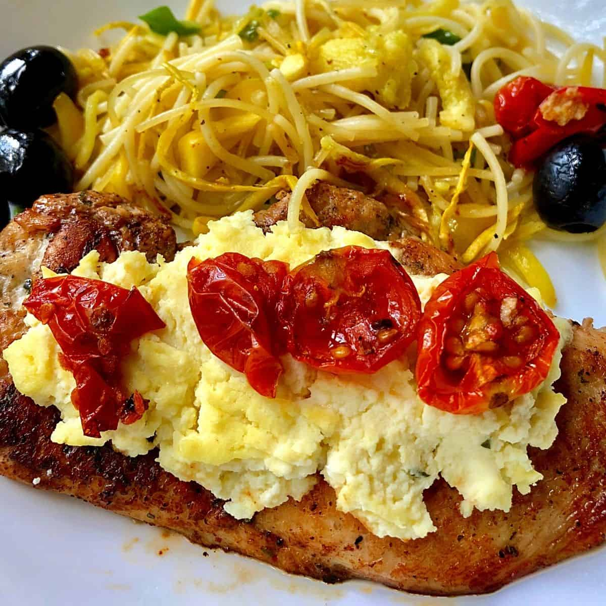 chicken breast with ricotta and tomatoes on white plate
