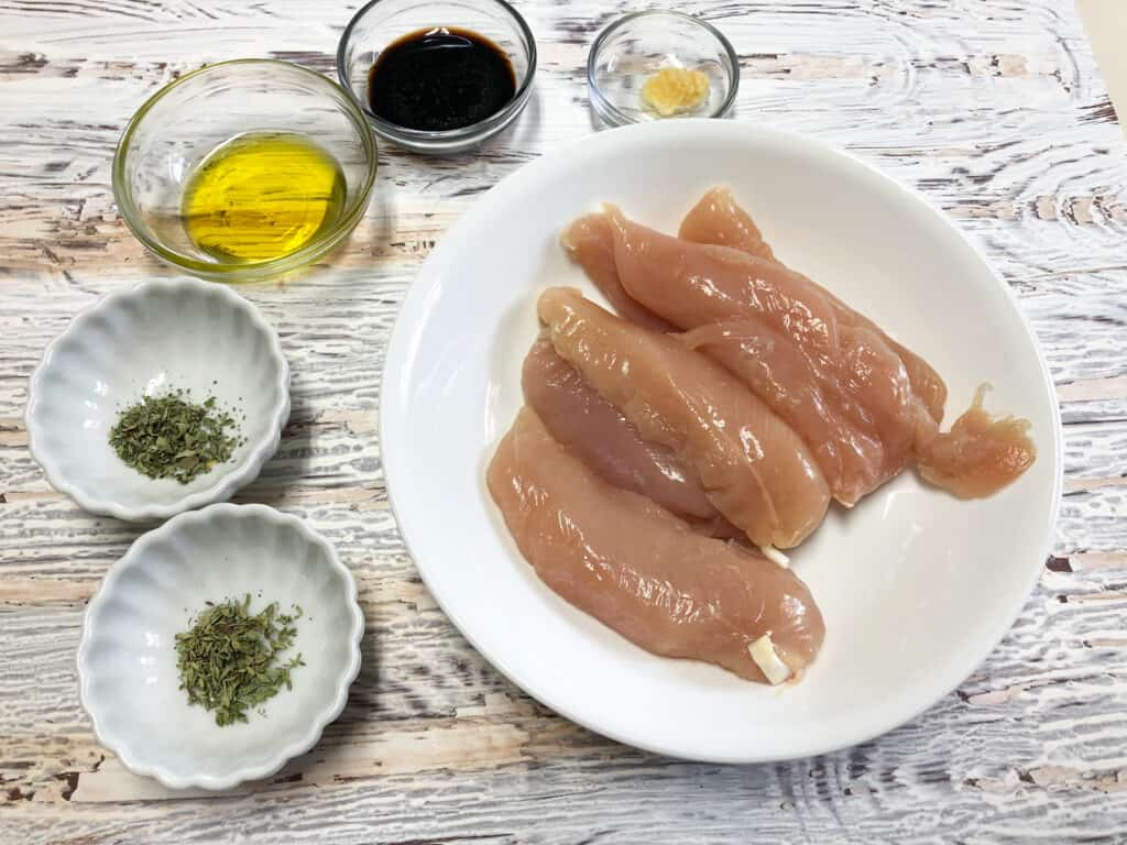 raw chicken tenders, herbs,oil in bowls
