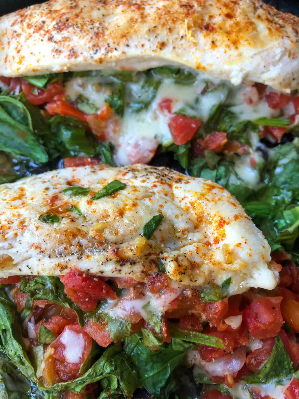 chicken breasts in skillet with spinach and rotel