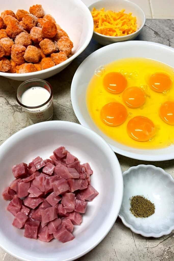 eggs, ham,sweet potato tots in white bowls