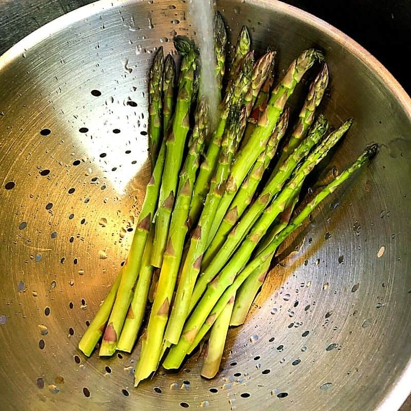 asparagus in colander with water