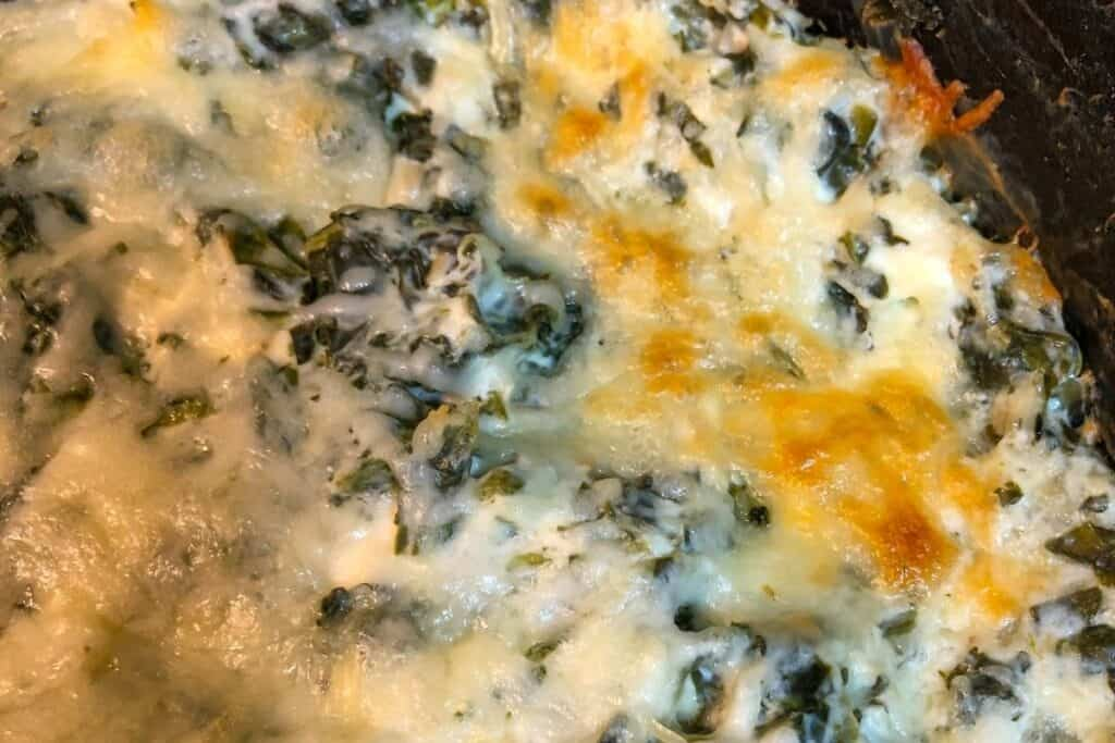 golden melted cheese and green spinach in black skillet