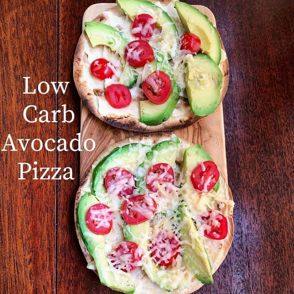 2 avocado pizza with sliced tomatoes on wooden cutting board