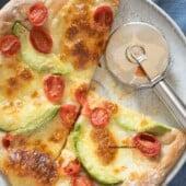 avocado tomato thin crust pizza with silver pizza cutter