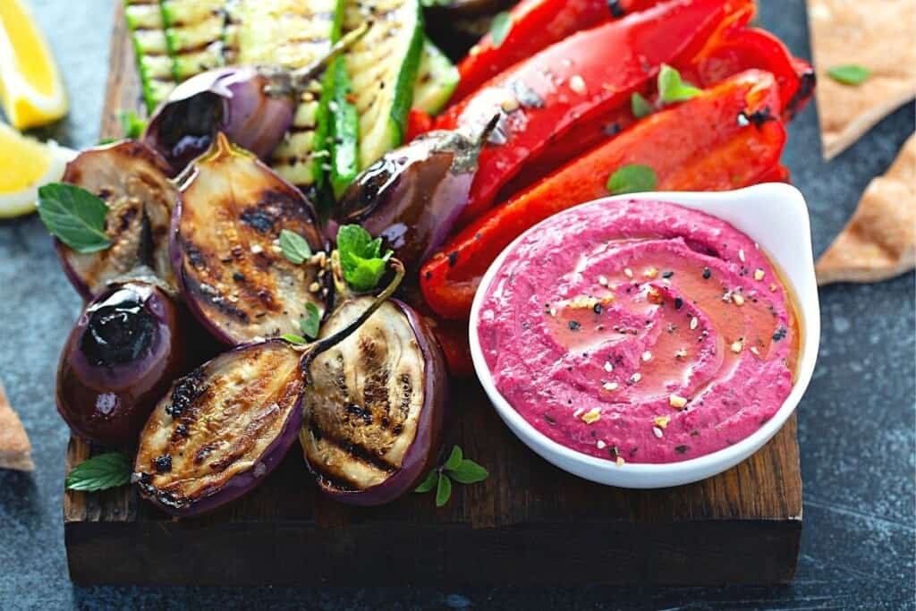 platter of grilled veggies with bowl of red hummus
