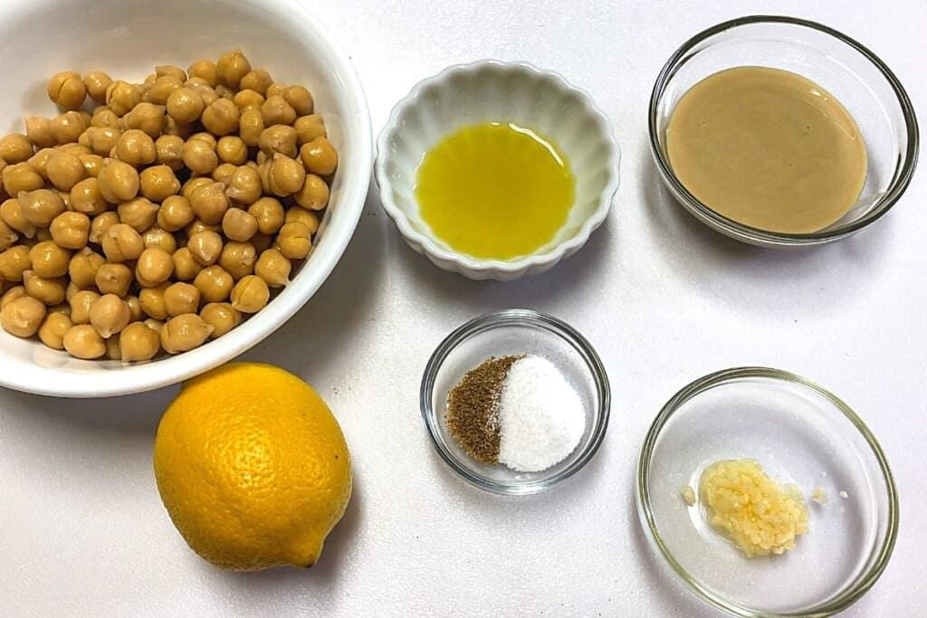 bowl of chickpeas, lemon,bowl of tahini, bowl of olive oil on white board