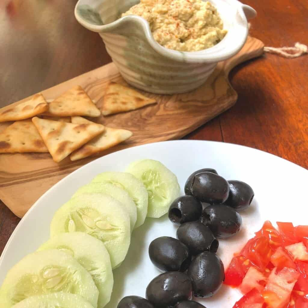 sliced cucumber, tomato, olives on white plate with pita crackers and bowl of hummus