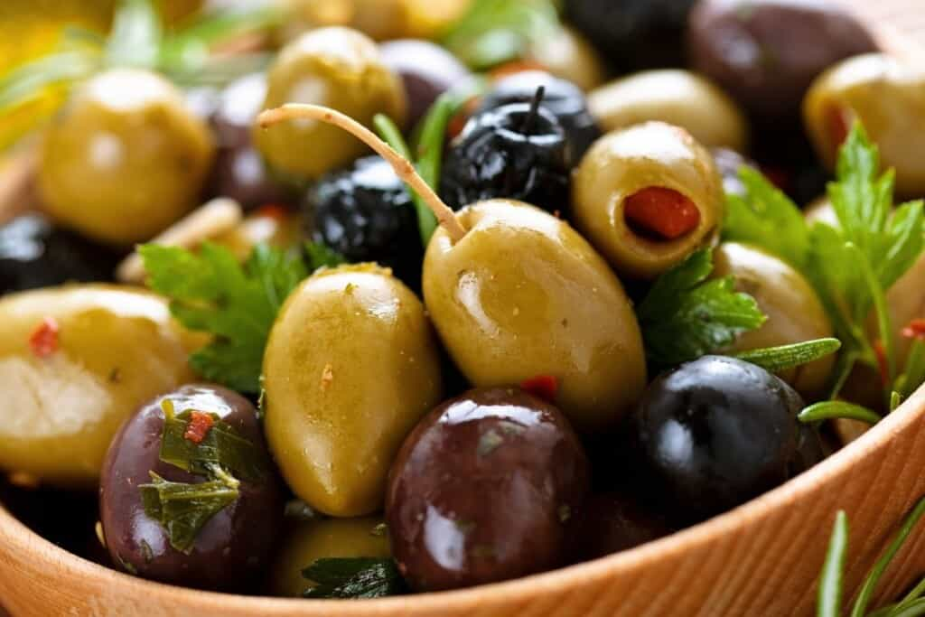 black, green and stuffed olives in brown bowl