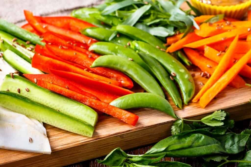 sliced red peppers, snow peas, carrots on brown board