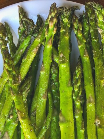 cooked asparagus on white plate