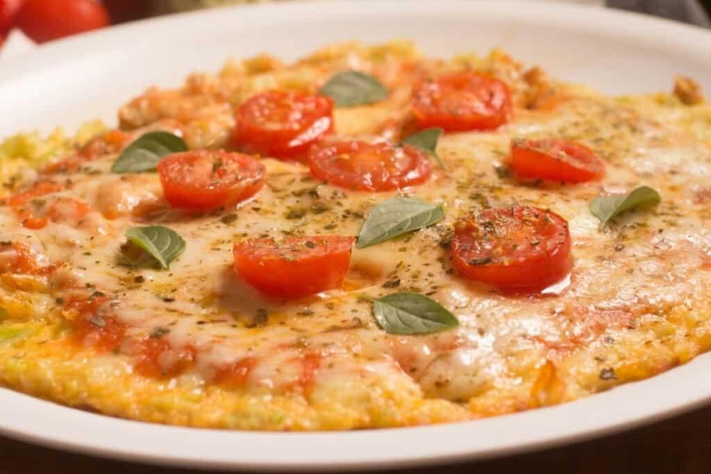 cauliflower crust pizza on white plate