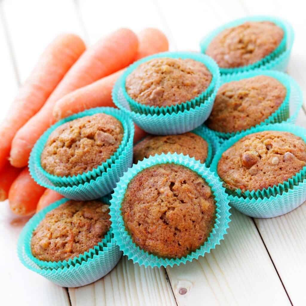 carrot muffins in turquoise cups with carrot sticks