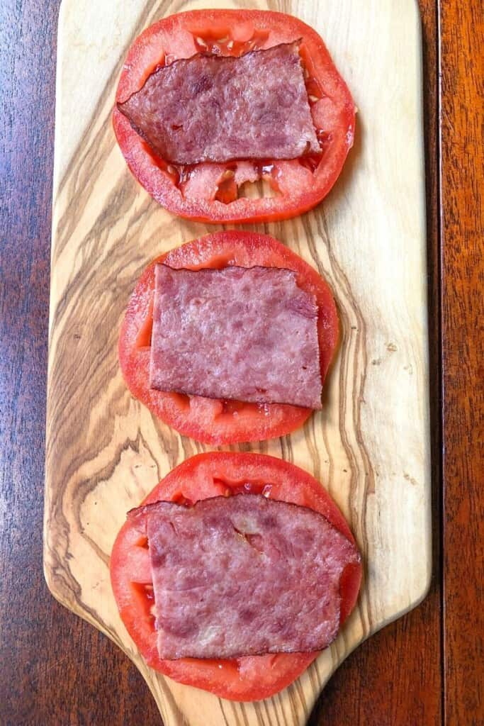 tomato slices topped with turkey bacon on wooden board