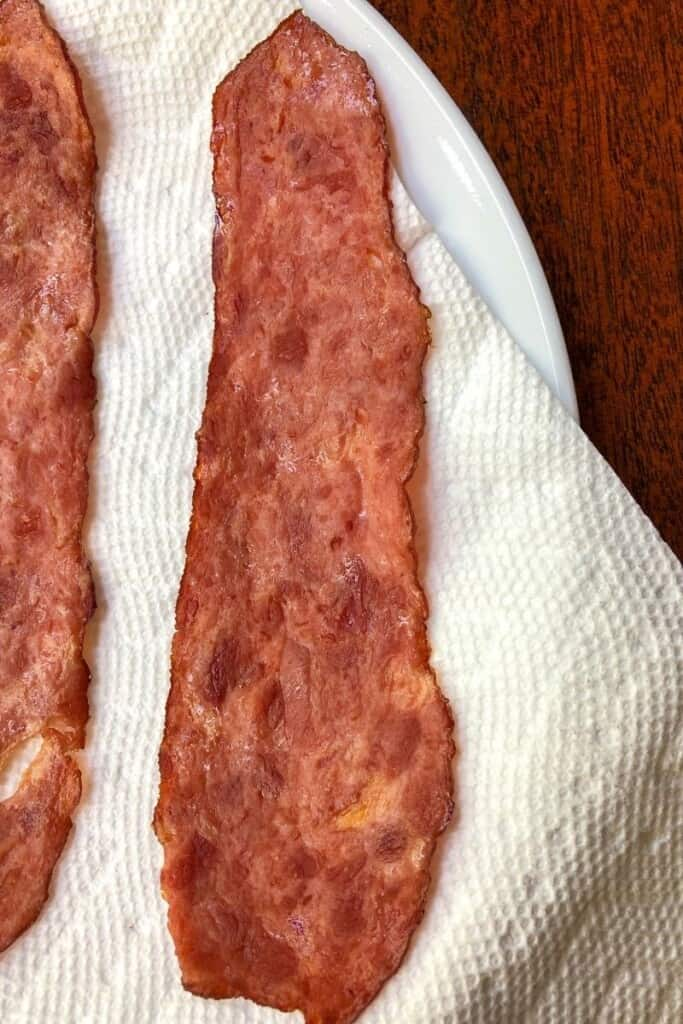 slice of cooked turkey bacon on paper towel