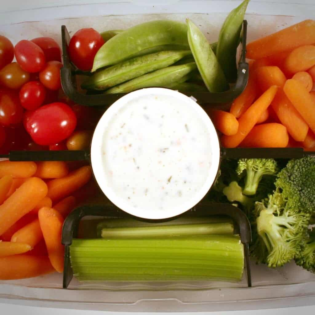 celery sticks, baby carrots, broccoli, cherry tomatoes with bowl of dip