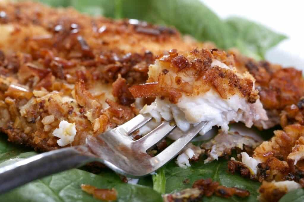 browned fish filet on lettuce with fork